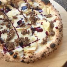 pizza con salsiccia, mela kanzi e riduzione di vino rosso